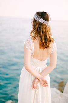 Panna młoda stoi nad brzegiem morza z rękami założonymi za plecami i spogląda w dal. wysokiej jakości zdjęcie