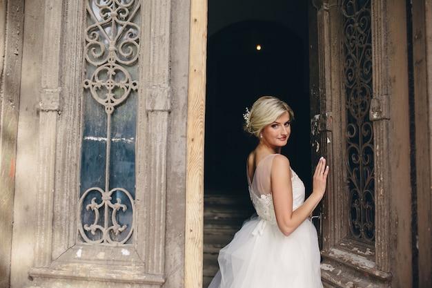 Panna młoda stoi przed starymi drzwiami