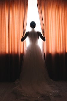Panna młoda stojąc przed oknem patrząc na zewnątrz