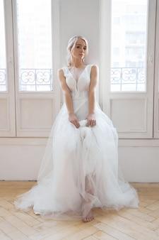 Panna młoda to kobieta w lekkiej letniej sukni ślubnej stojąca przy oknie