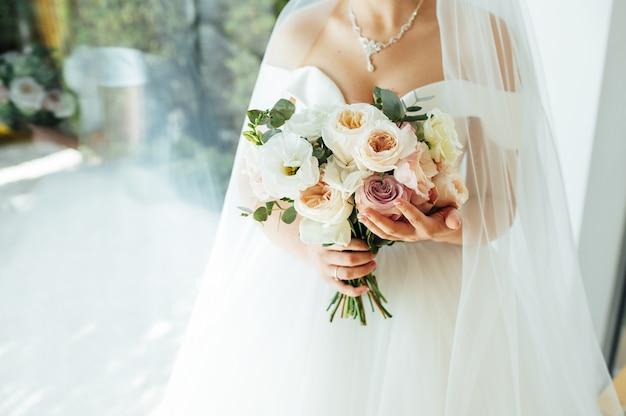 Panna młoda trzyma biały ślubny bukiet róż i miłość kwiat