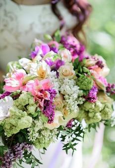 Panna młoda trzyma bogaty bukiet ślubny wykonany z białych i fioletowych kwiatów