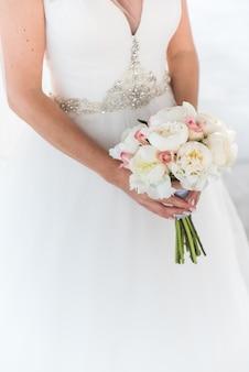 Panna młoda trzyma bukiet białe peonie i róże.