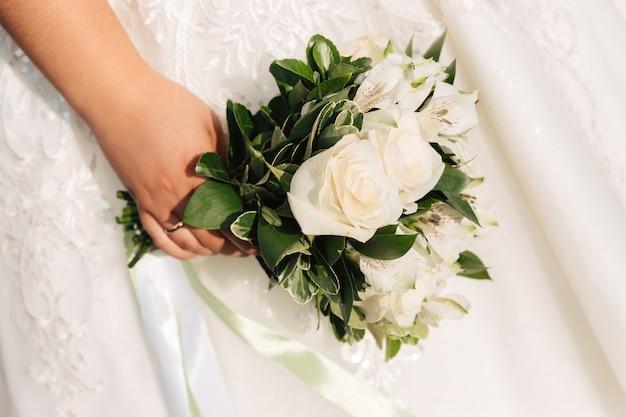 Panna młoda trzyma bukiet białych róż na tle białej sukni ślubnej.