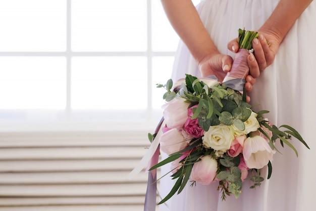 Panna młoda trzyma bukiet kwiatów