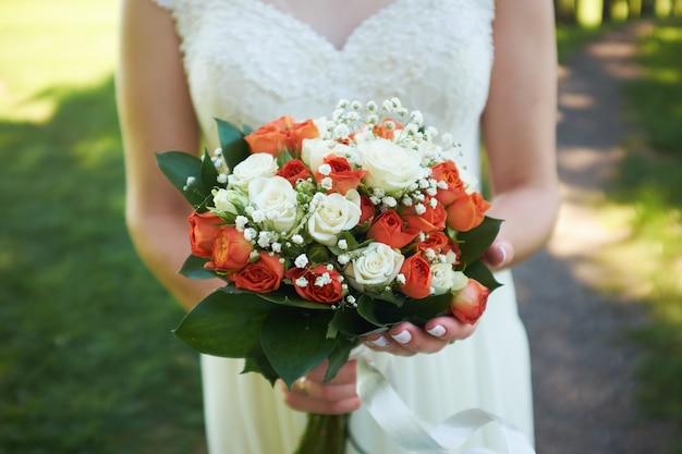 Panna młoda trzyma bukiet pomarańczowych róż