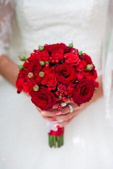 Panna młoda trzyma bukiet róż