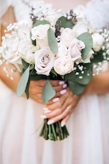 Panna młoda trzyma bukiet ślubny. delikatny bukiet ślubny w odcieniach bieli i bzu.