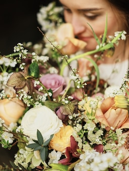 Panna młoda trzyma bukiet ślubny i wącha kwiaty z bliska, duży piękny bukiet