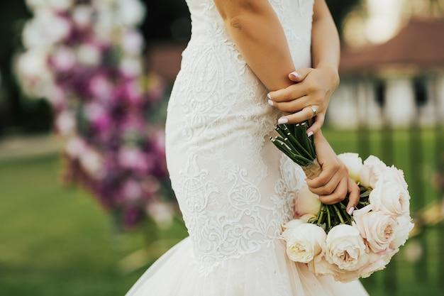 Panna młoda trzyma bukiet ślubny, suknię ślubną, szczegóły ślubne.