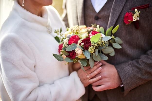 Panna młoda trzyma bukiet ślubny w rękach stojących w pobliżu pana młodego