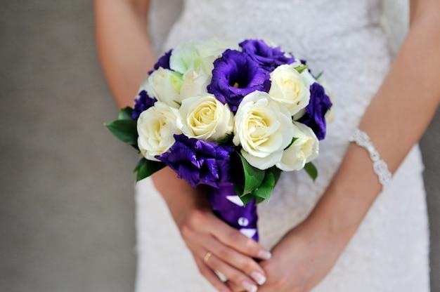 Panna młoda trzyma bukiet ślubny z białymi i liliowymi różami