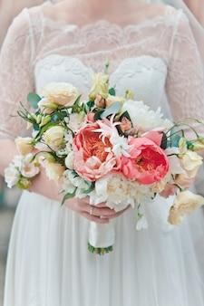 Panna młoda trzyma bukiet świeżych wiosennych i letnich kwiatów w pastelowych kolorach