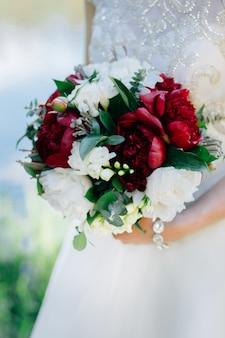 Panna młoda trzyma dużego i pięknego ślubnego bukiet