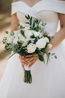 Panna młoda trzyma jej bukiet ślubny