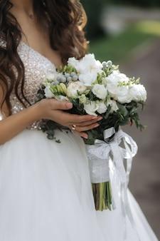 Panna młoda trzyma piękny bukiet ślubny z białymi różami i piwoniami