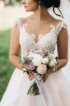 Panna młoda trzyma piękny bukiet ślubny z różami i piwoniami