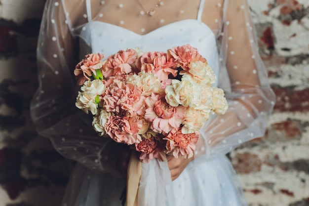 Panna młoda trzyma piękny bukiet ślubny.