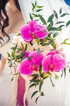 Panna młoda trzyma piękny ślubny bukiet róż i wibrujących orchidei