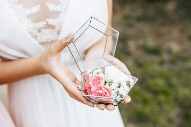 Panna młoda trzyma pudełko ślubne na pierścionki z białymi i różowymi kwiatami