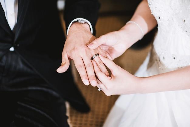 Panna młoda trzyma rękę pana młodego, pokazując obrączki ślubne