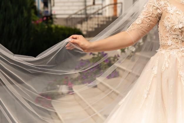 Panna młoda trzyma ślubną przesłonę przy dniem ślubu