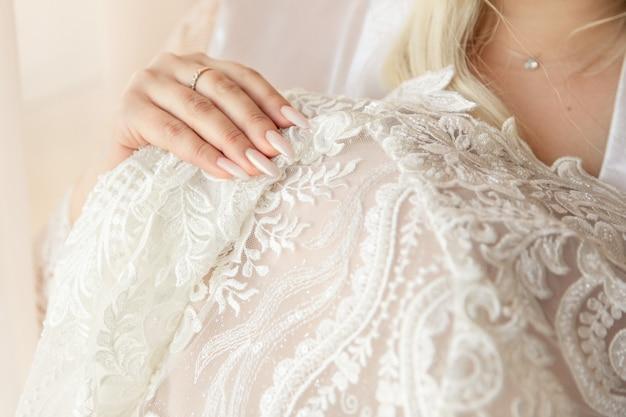 Panna młoda trzyma ślubną suknię przy dniem ślubu