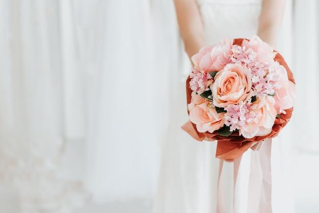 Panna młoda trzyma ślubnego bukiet w ręce