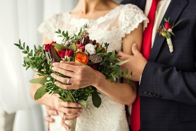 Panna młoda trzyma ślubnego bukiet w rękach stoi blisko fornala