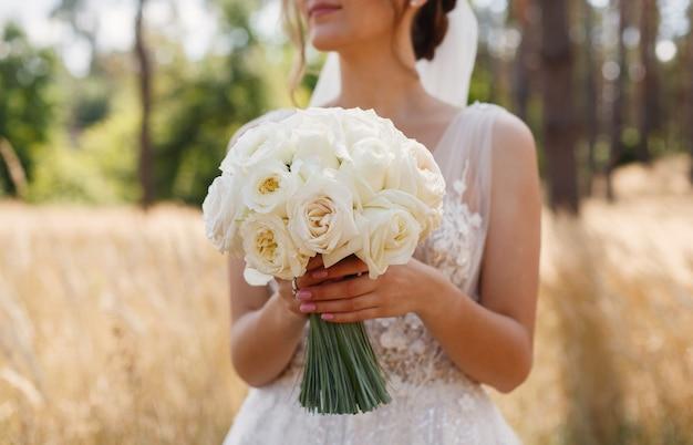Panna młoda trzyma ślubny bukiet białych kwiatów na zewnątrz młodej dziewczyny w białej sukni