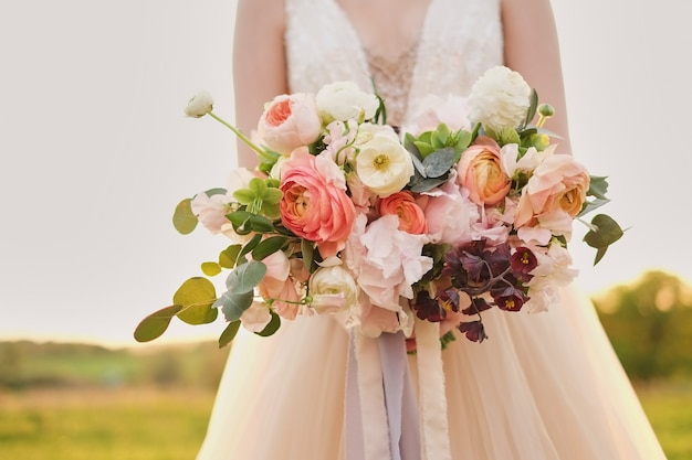 Panna młoda trzyma ślubny bukiet w pastelowych różowych kolorach.