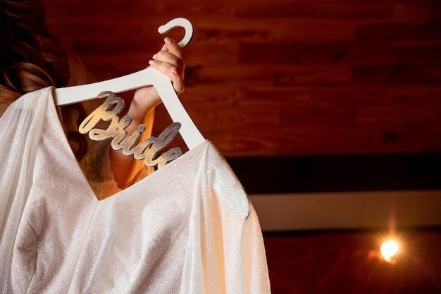 """Panna młoda trzyma suknię ślubną z napisem """"panna młoda"""""""