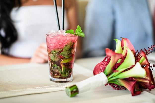 Panna młoda trzyma szklankę mojito, bukiet ślubny na stole w restauracji