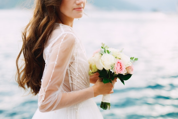 Panna młoda trzyma w dłoniach bukiet róż i stoi na molo w zatoce kotorskiej z bliska. wysokiej jakości zdjęcie
