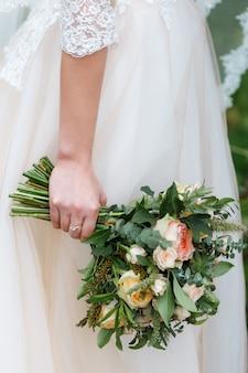 Panna młoda trzyma w dłoniach delikatny, drogi, modny ślubny bukiet zieleni i róż. klasyczne kwiaty ślubne w kolorach pomarańczowym i różowym