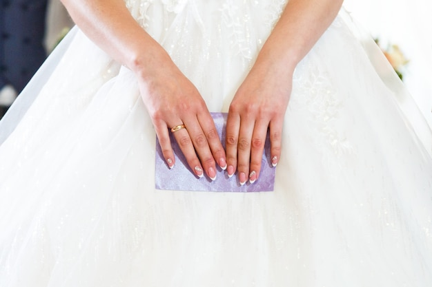 Panna młoda trzyma w rękach fioletową kopertę, francuski manicure