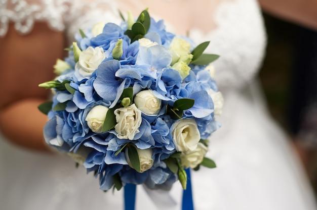 Panna młoda trzyma w ręku piękny ślubny bukiet róż i niebieskich hortensji