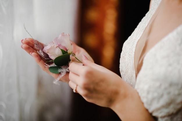 Panna młoda trzyma w ręku z bliska kwiaty butonierki pana młodego oraz zieleń i zieleń.
