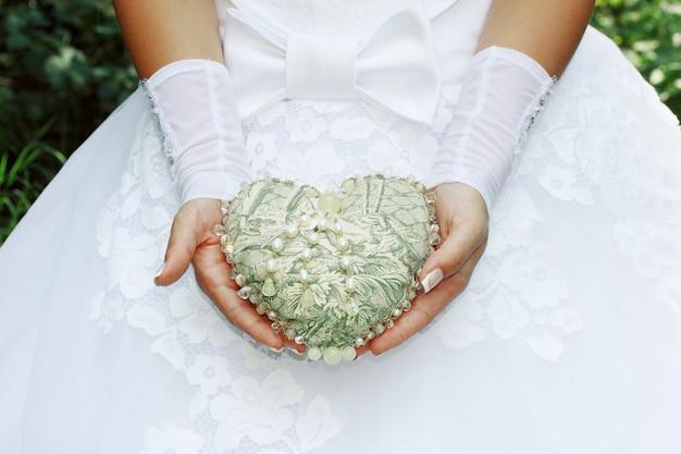 Panna młoda trzyma zabytkowe serce ozdobione perłami