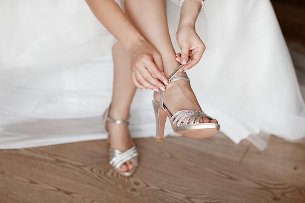 Panna młoda ubiera buty przed ślubem. poranek panny młodej. zbliżenie szczegół panny młodej kładzenie na szpilkach sandała ślubu butach. buty ślubne panny młodej. piękne nogi