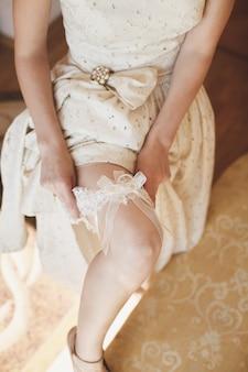 Panna młoda ubiera podwiązkę na nogawce