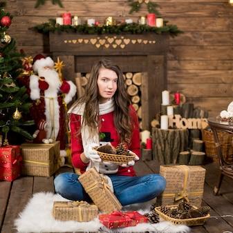 Panna młoda uroda moda w zimie radosna dziewczyna kobieta ubrana w zimowe ubrania, siedząc w pobliżu choinki, trzymając pudełko.
