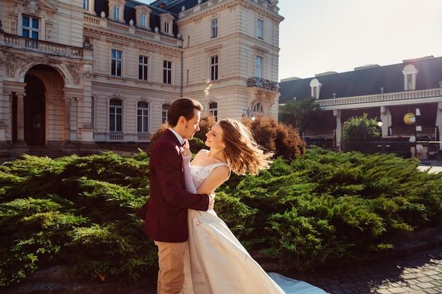 Panna młoda uśmiecha się do pana młodego w pobliżu starego pałacu