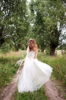 Panna młoda w białej jasnej sukni ślubnej z bukietem ślubnym spacerująca wśród drzew i tańcząca