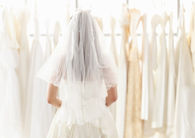 Panna młoda w białej koronkowej sukni ślubnej stoi z tyłu i patrzy na suknię ślubną w przymierzalni. kobieta wybierająca wiele sukien ślubnych w sklepie.