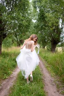 Panna młoda w białej llight sukni ślubnej z bukietem ślubnym ucieka w pasie drzew