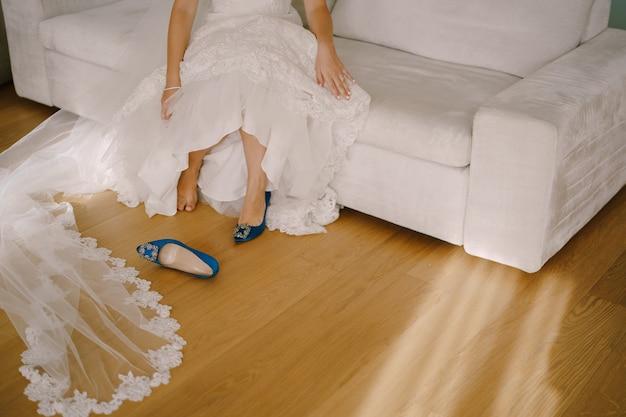 Panna młoda w białej sukience siedzi na kanapie i zdejmuje but