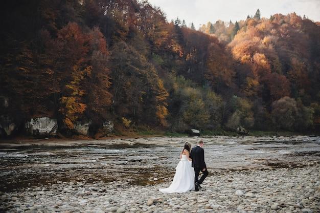 Panna młoda w białej sukni i pana młodego idzie do skał rzeki i trzyma się za ręce