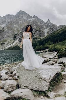 Panna młoda w białej sukni i pana młodego, stojący w pobliżu rzeki i przytulanie i słońce