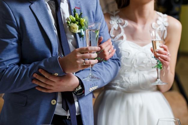 Panna młoda w białej sukni i pana młodego w niebieskim garniturze trzymają w rękach kieliszki do szampana